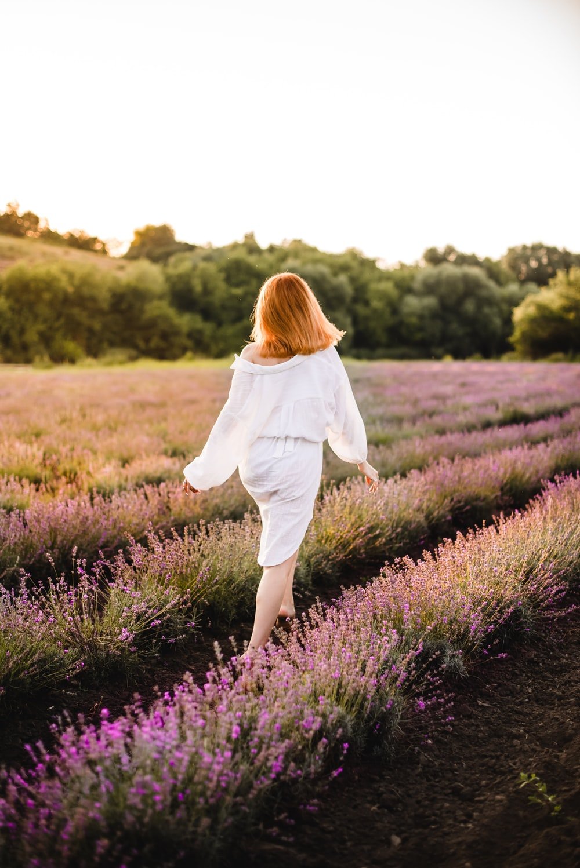 woman in white long sleeve shirt walking on purple flower field during daytime