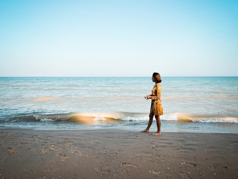 girl in brown dress standing on beach during daytime