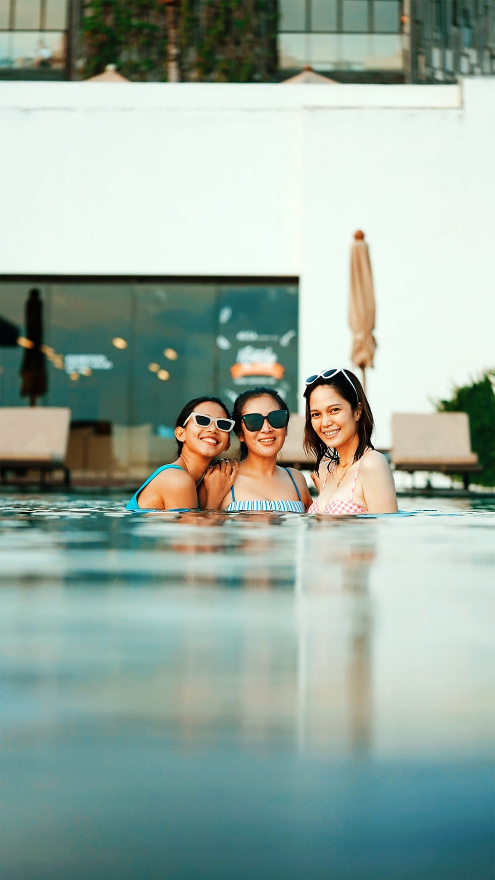 woman in black sunglasses on swimming pool during daytime
