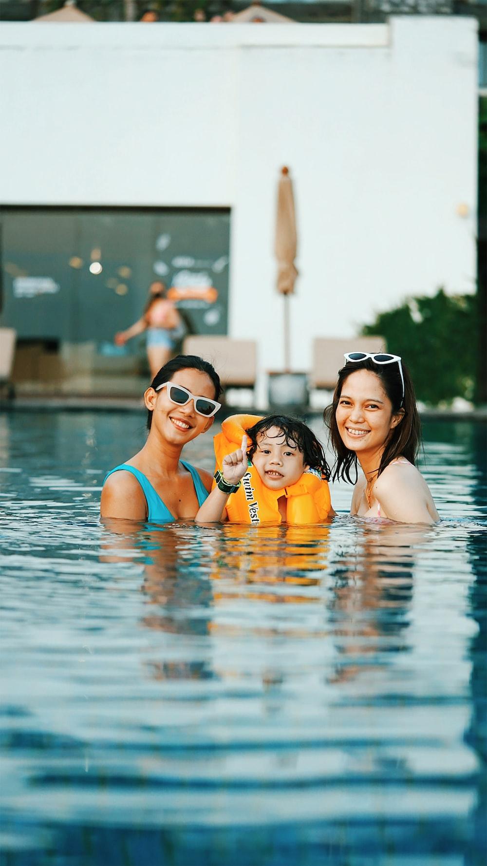 2 women in swimming pool posing for photo
