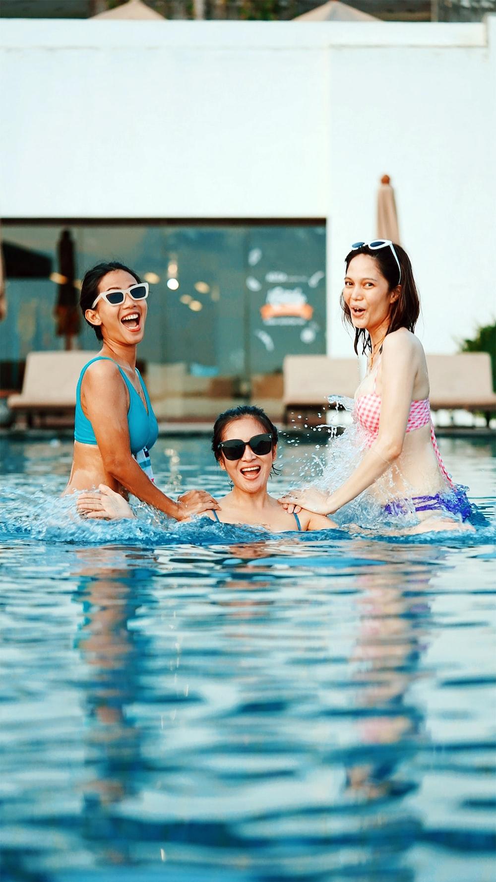 2 women in swimming pool during daytime