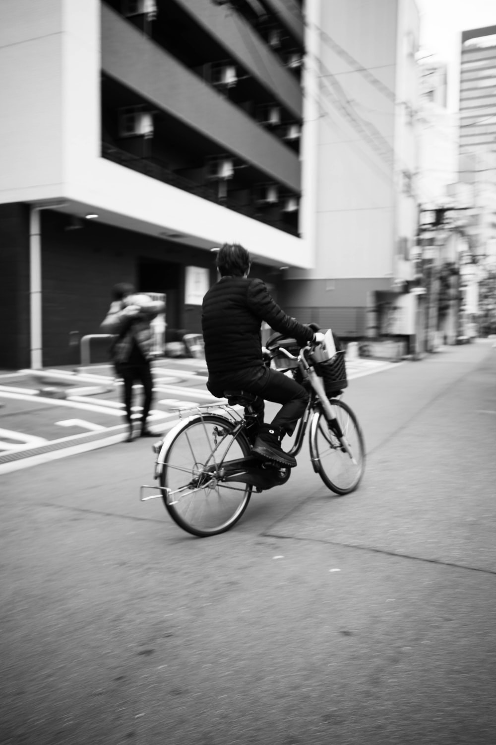 man in black jacket riding bicycle in grayscale photography