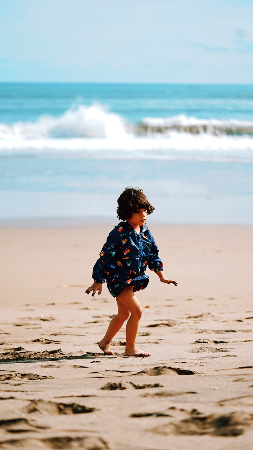 girl in blue and white floral dress walking on beach during daytime