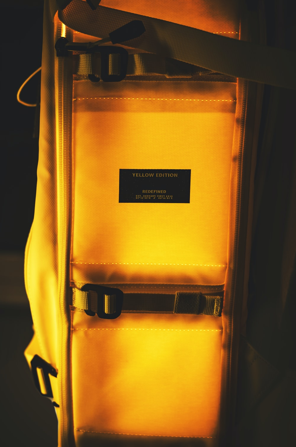 yellow and black bag on black textile