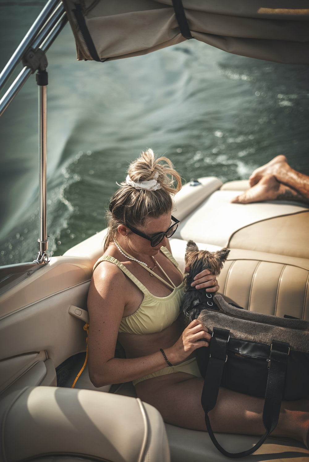 woman in gray tank top sitting on white and black boat during daytime