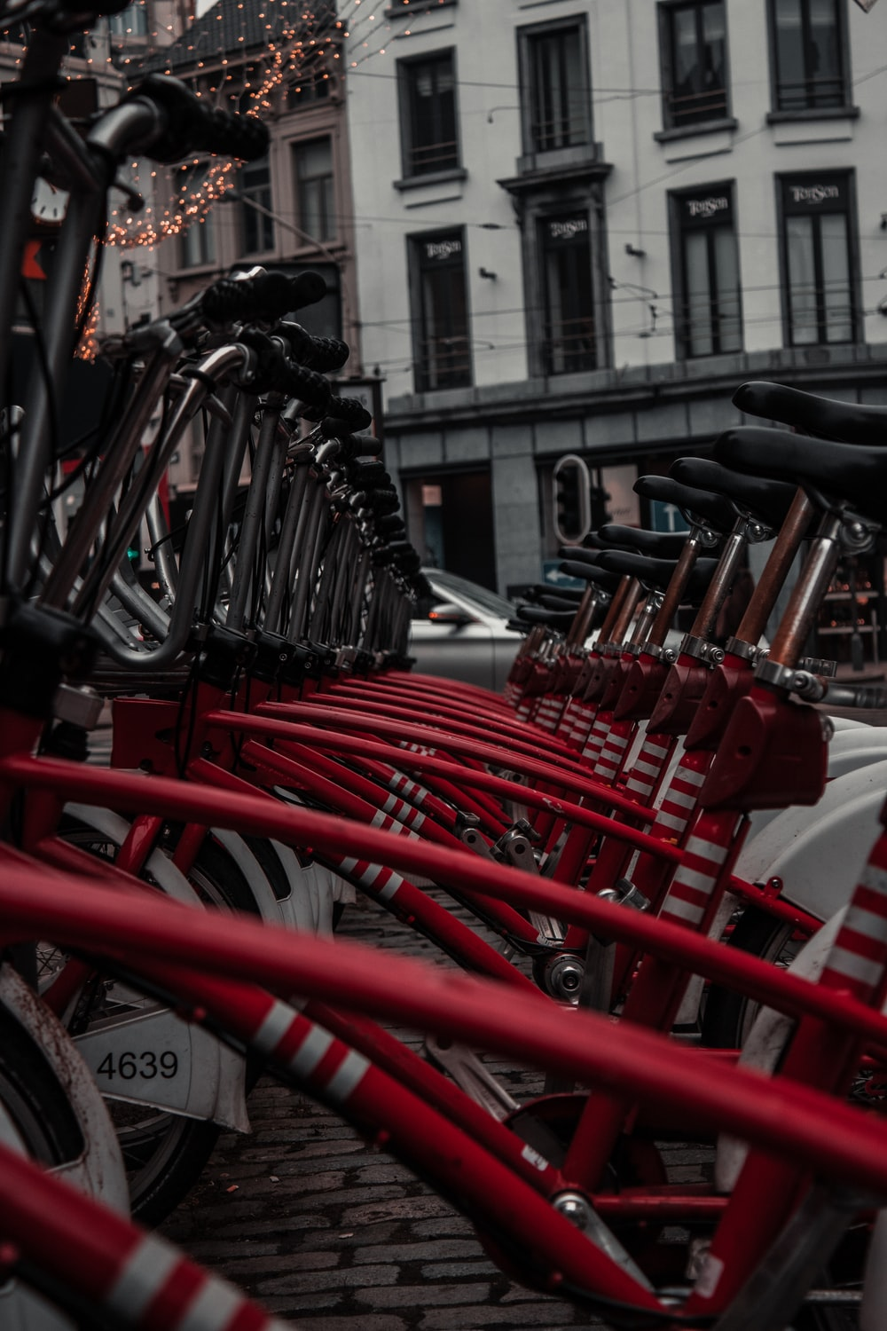 red and black bicycle parked on sidewalk during daytime