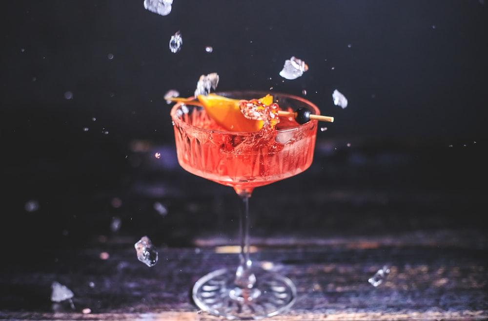orange liquid in clear wine glass
