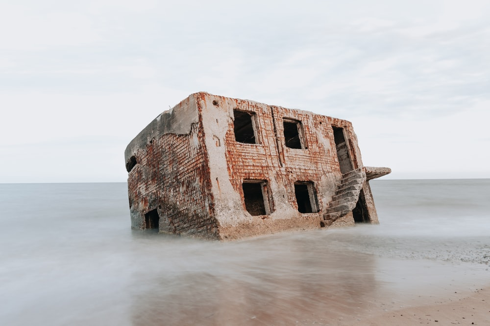 brown concrete building on sea shore during daytime