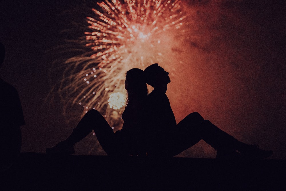 silhouette of man and woman kissing under fireworks