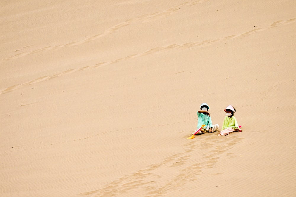 2 children in green and yellow wet suit walking on brown sand during daytime