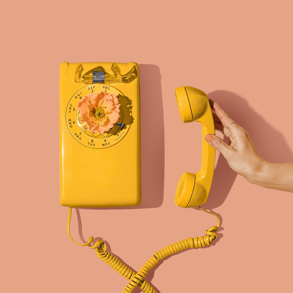 yellow and red telephone on yellow surface