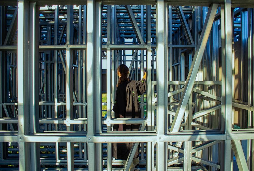 man in black jacket standing on gray metal frame