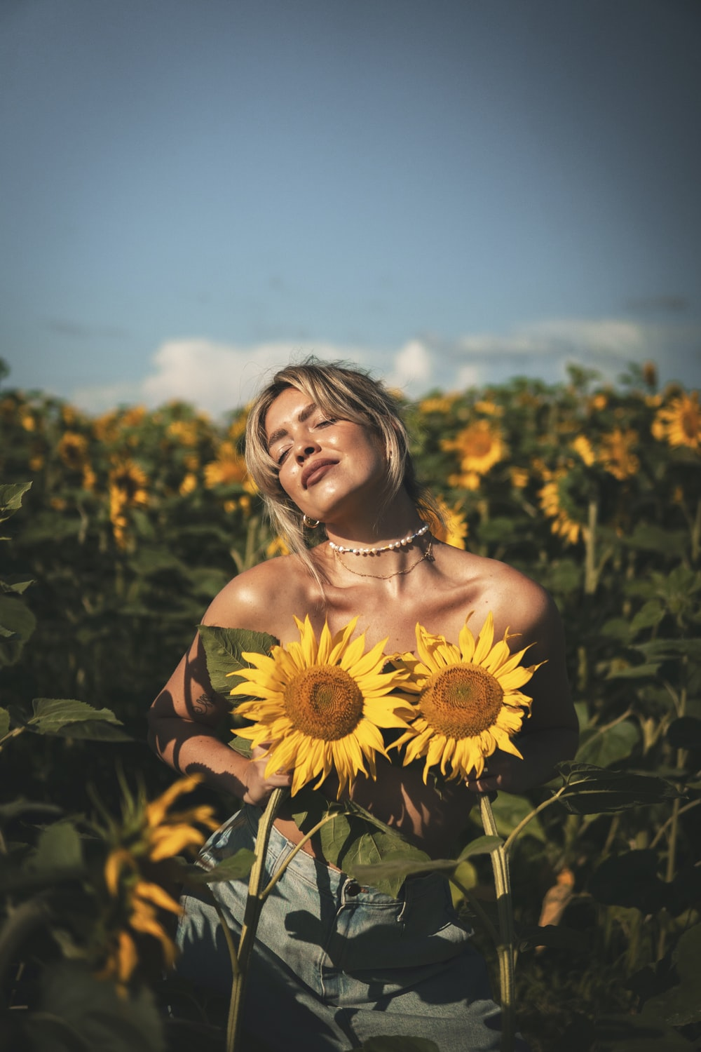 woman in red off shoulder dress holding sunflower