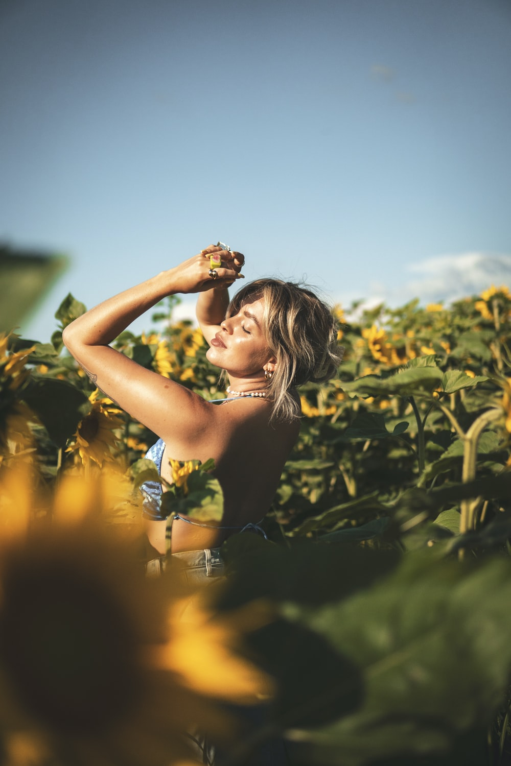 woman in yellow floral tank top standing on green grass field during daytime