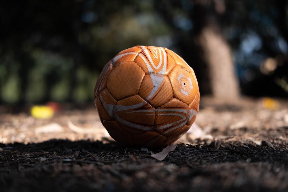 orange soccer ball on ground