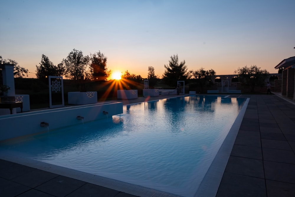swimming pool near trees during sunset