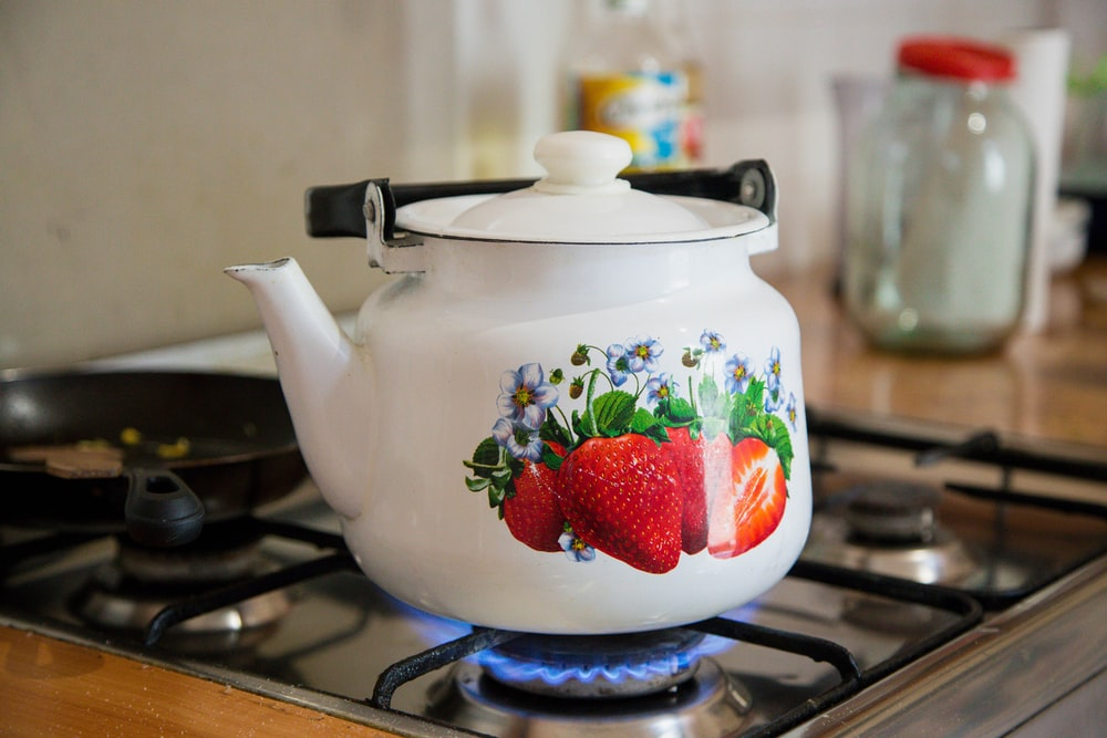 white and red strawberry print ceramic teapot on stove