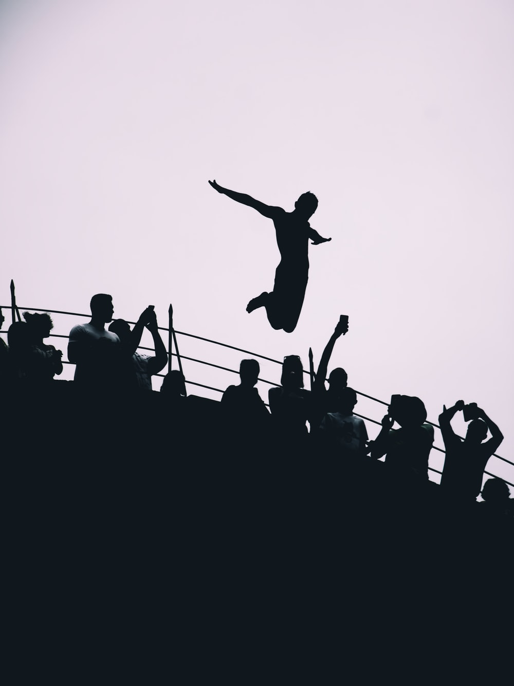silhouette of people jumping during daytime