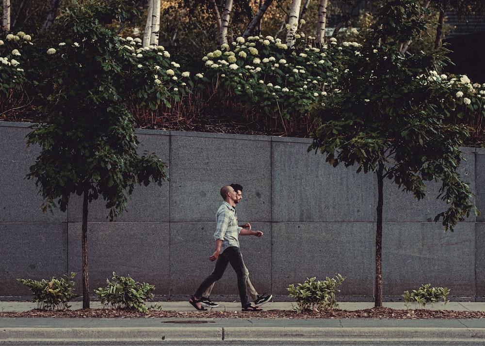 boy in white t-shirt and black pants walking on sidewalk during daytime