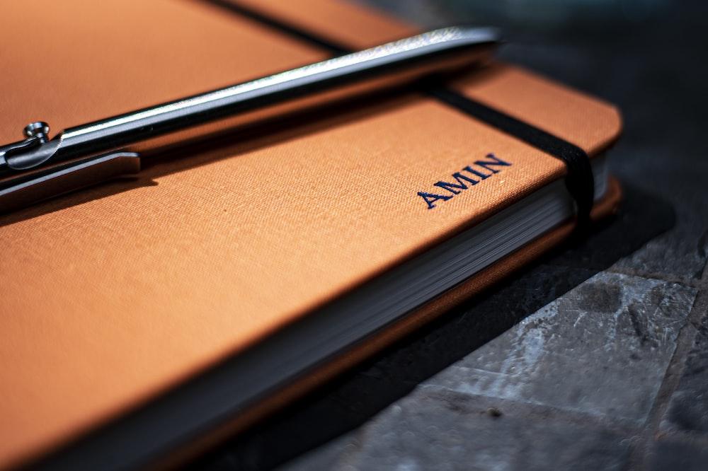 black pen on orange book