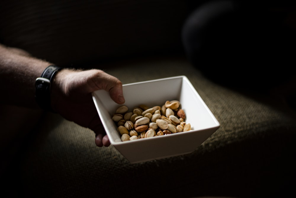 person holding brown and white nuts in white box