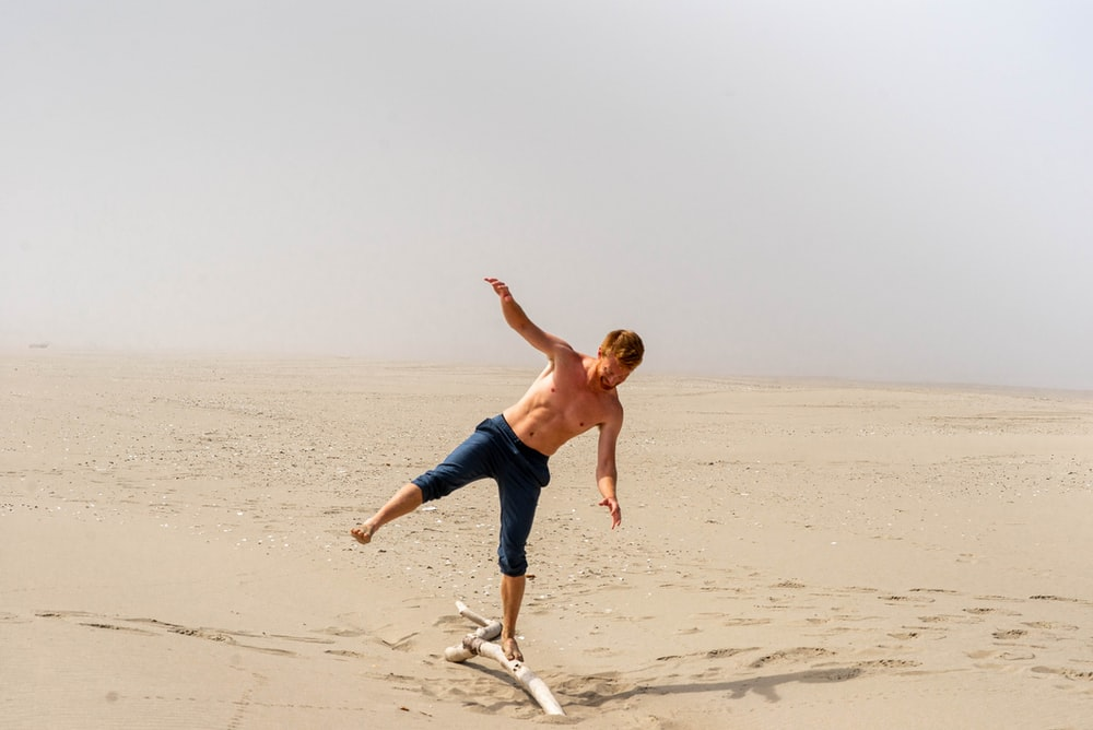 man in blue shorts running on beach during daytime