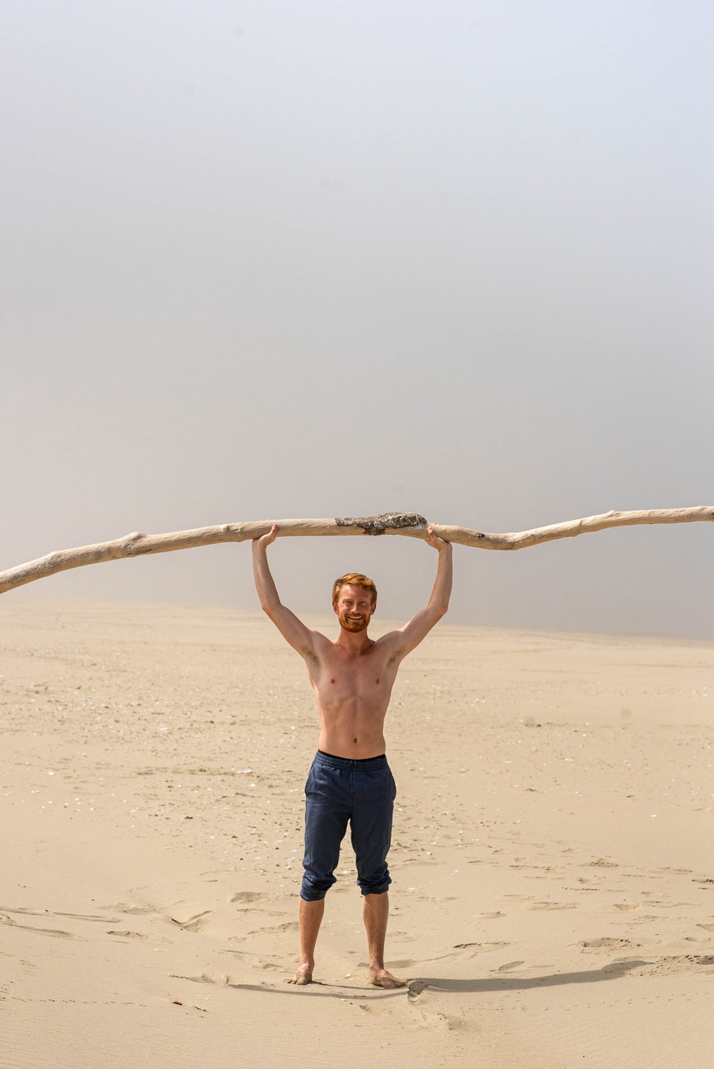 topless man in black shorts standing on brown sand during daytime