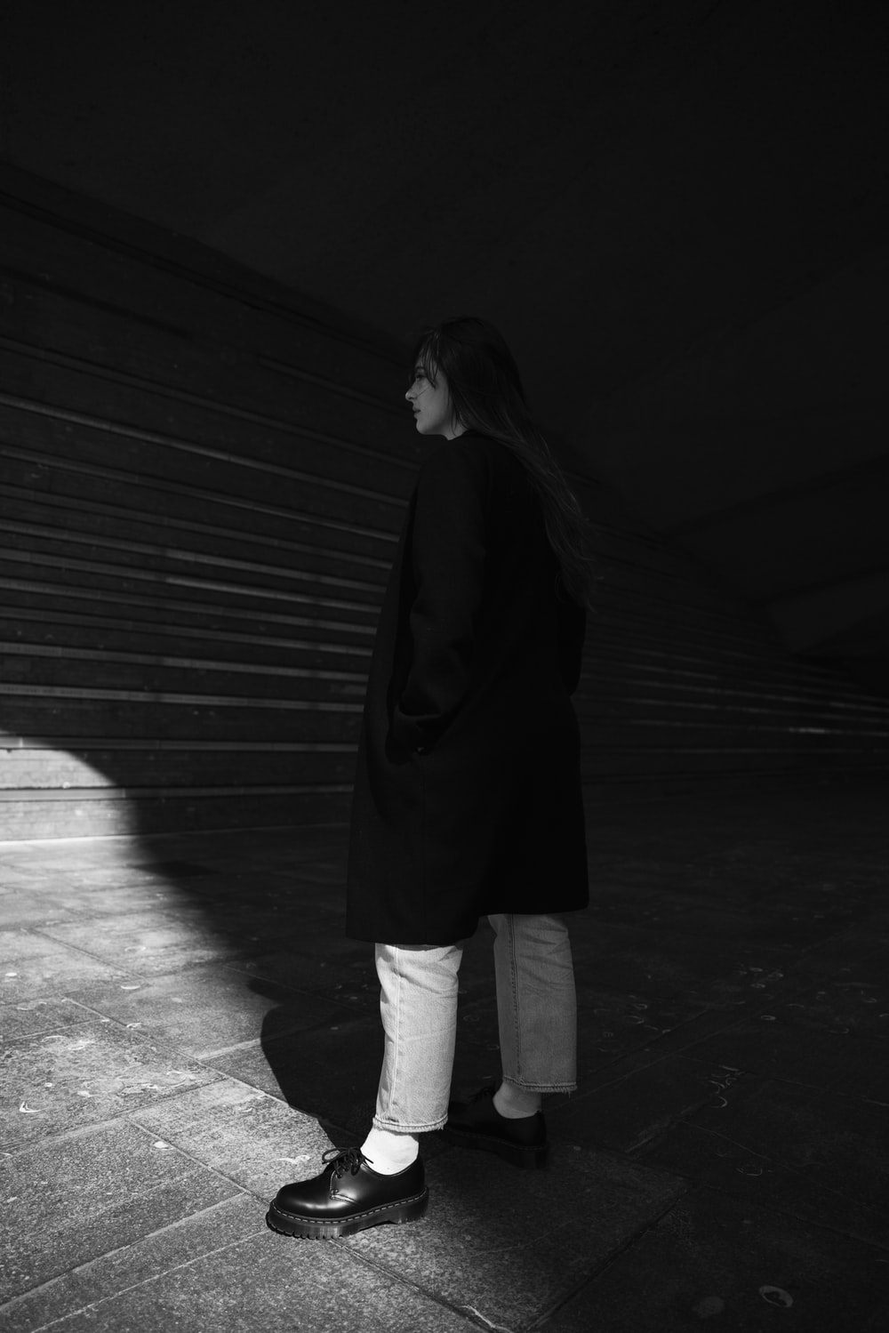 woman in black coat and white pants standing on the sidewalk