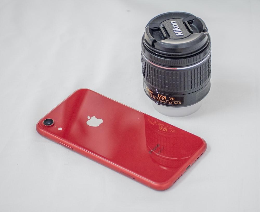 red iphone case beside black camera lens
