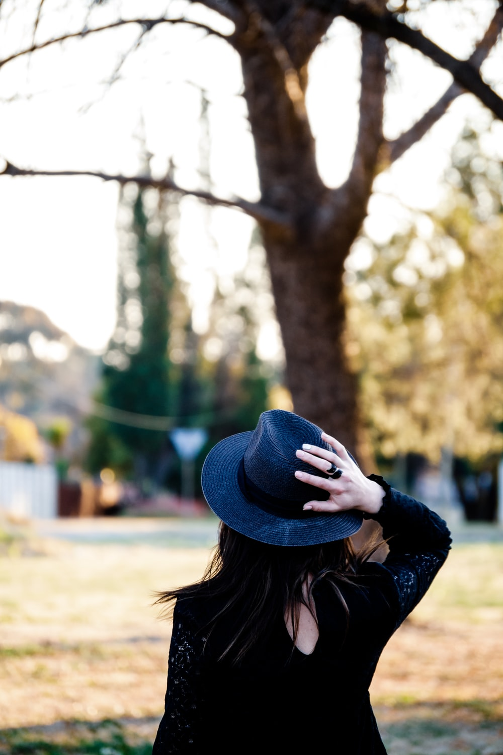 woman in blue hat and black long sleeve shirt standing near trees during daytime