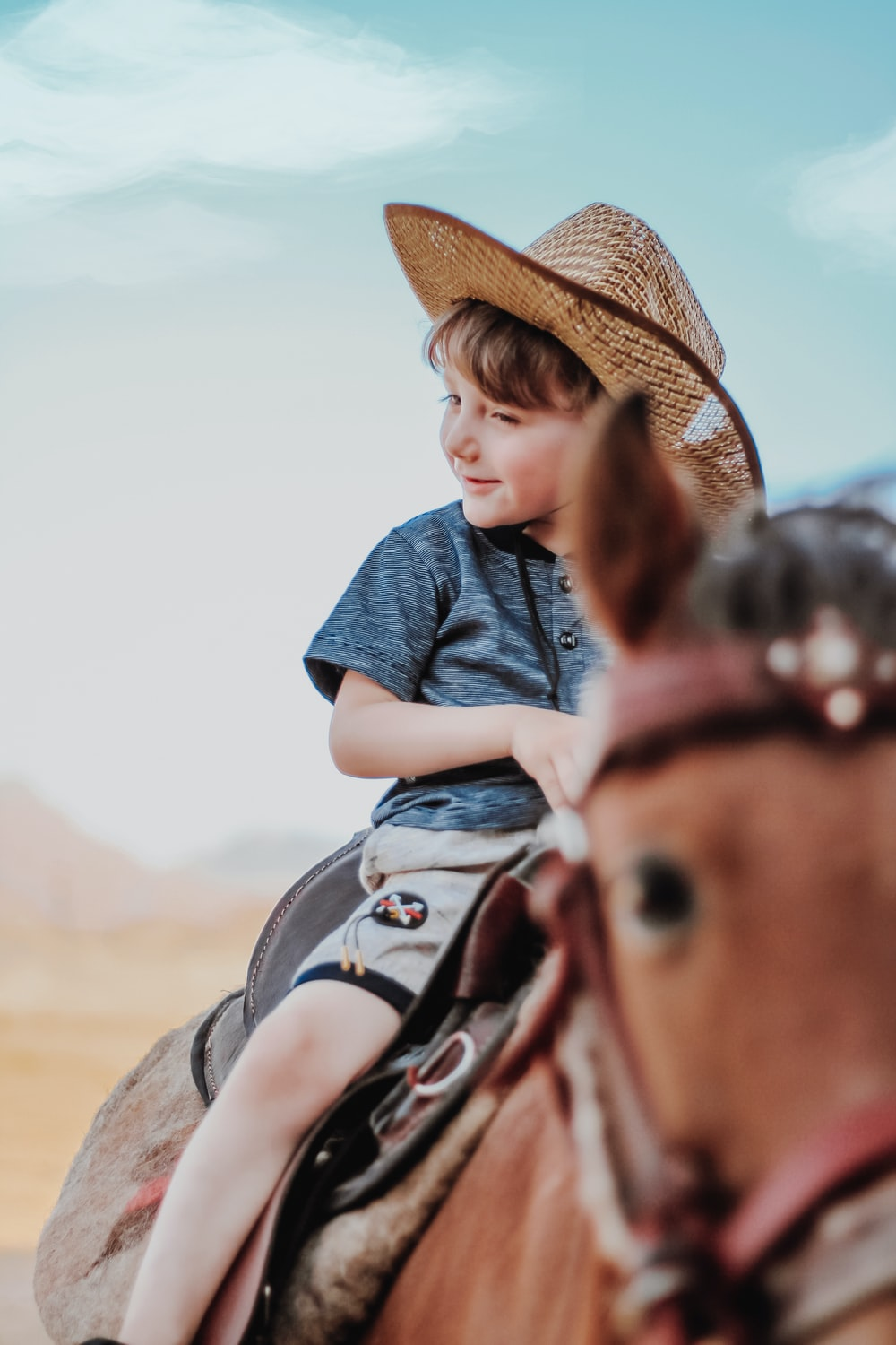 woman in blue denim jacket and brown cowboy hat riding brown horse during daytime