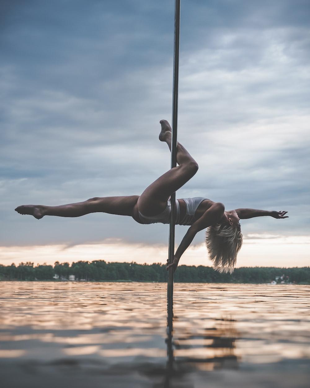 woman in black bikini on black metal pole during daytime