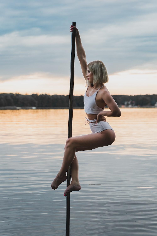 woman in white bikini sitting on pole on water during daytime