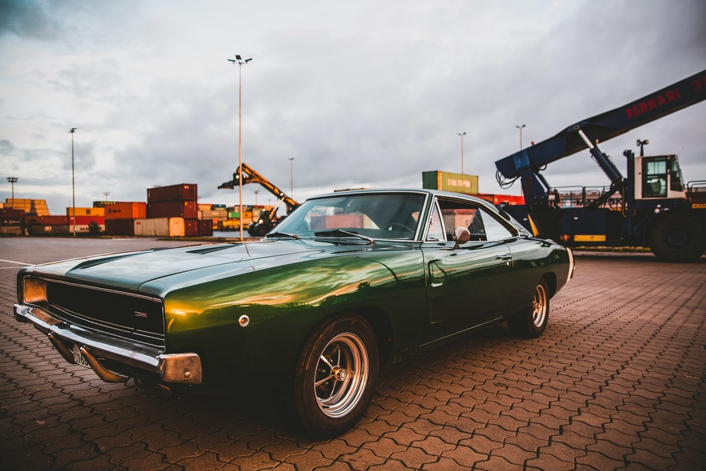 green chevrolet camaro parked on parking lot during daytime