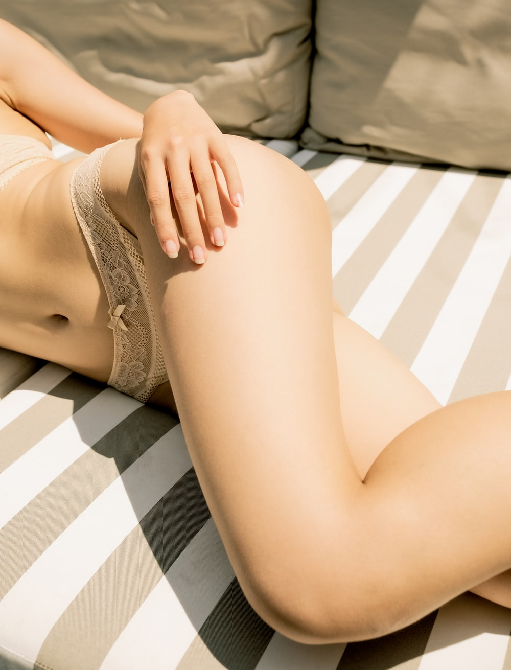 woman in beige panty lying on white and black stripe bed