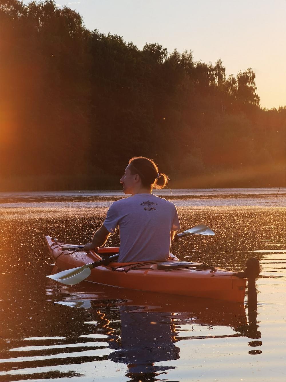 man in blue shirt riding red kayak on sea shore during sunset