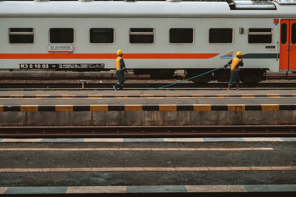 white red and blue train on rail track