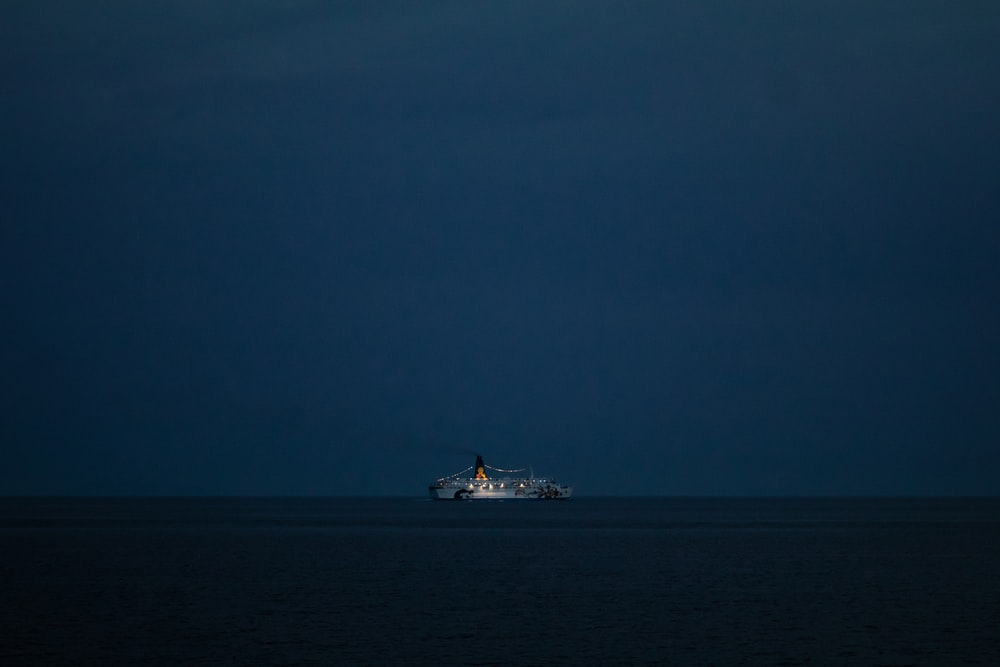 white ship on sea under gray sky