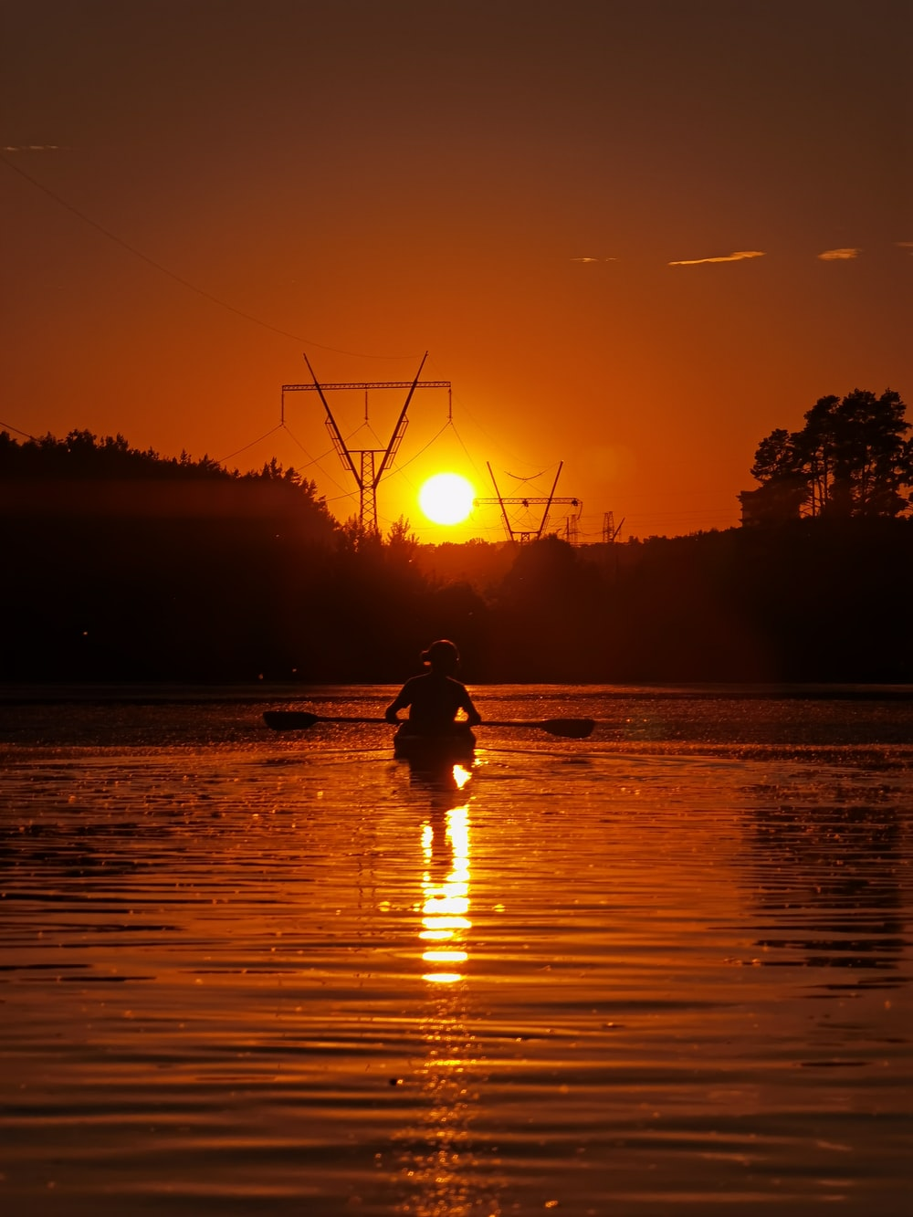 silhouette of person riding on horse on water during sunset