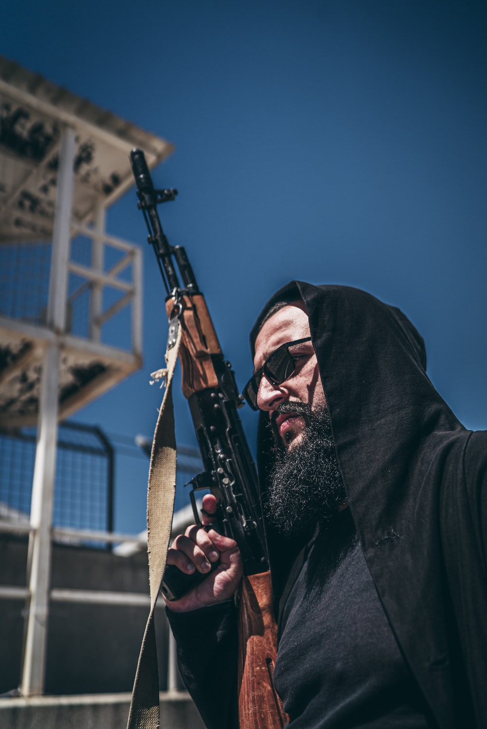 man in black coat holding black rifle