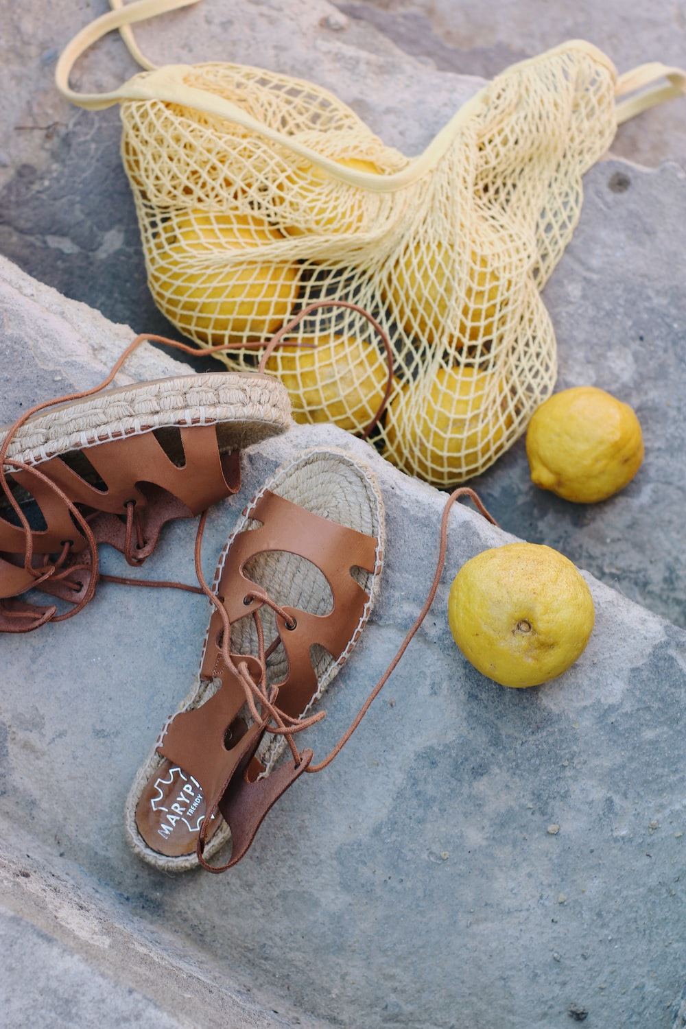yellow lemon beside brown leather sandals