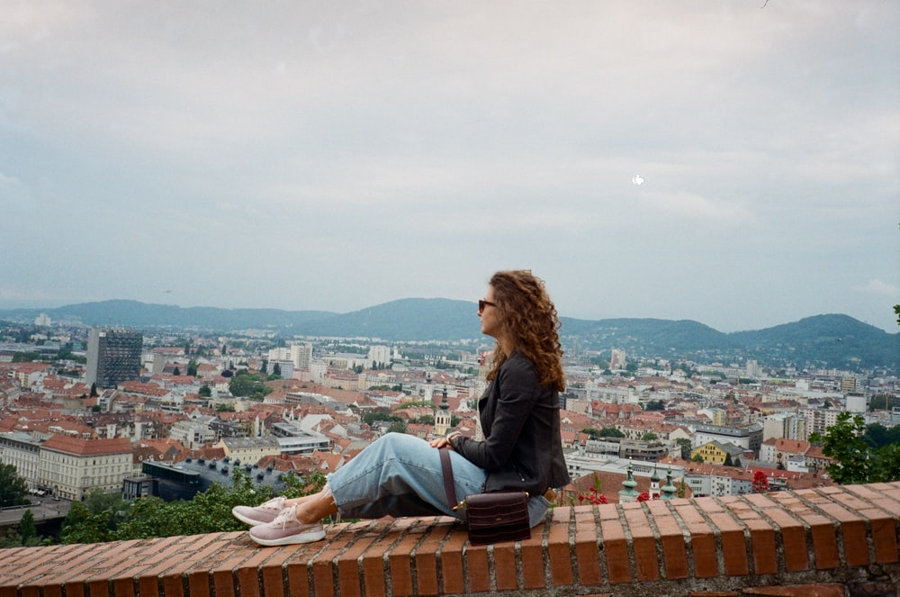 woman in blue denim jacket sitting on brown roof top during daytime