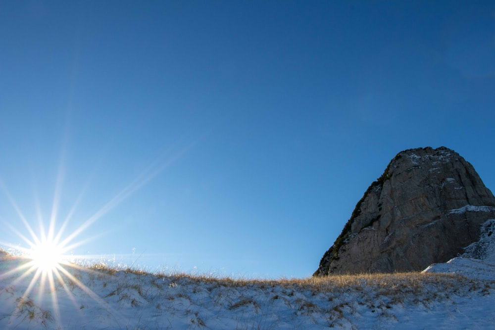 brown rock formation on white snow field under blue sky during daytime