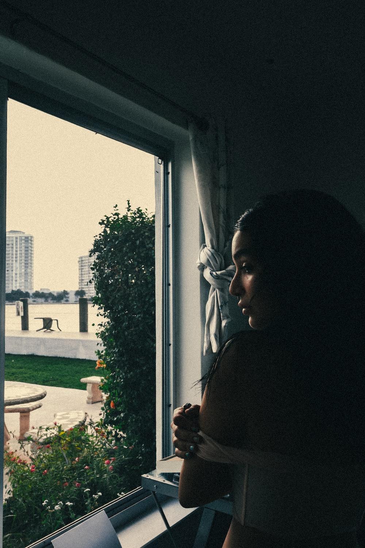 woman in black shirt standing near window