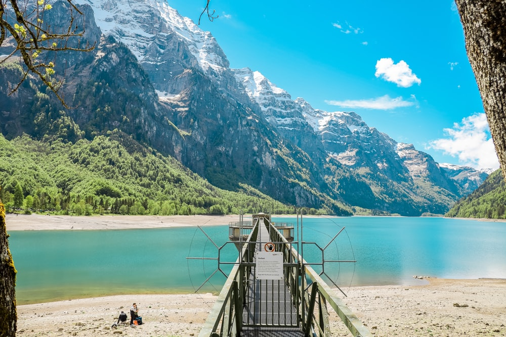 brown wooden bridge on lake near mountain range