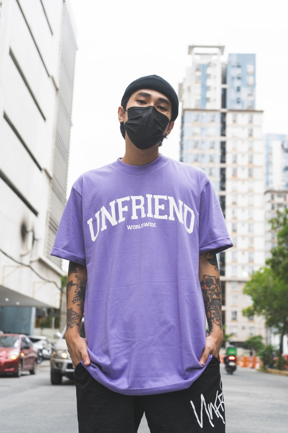 man in purple crew neck t-shirt wearing black sunglasses standing near white concrete building during