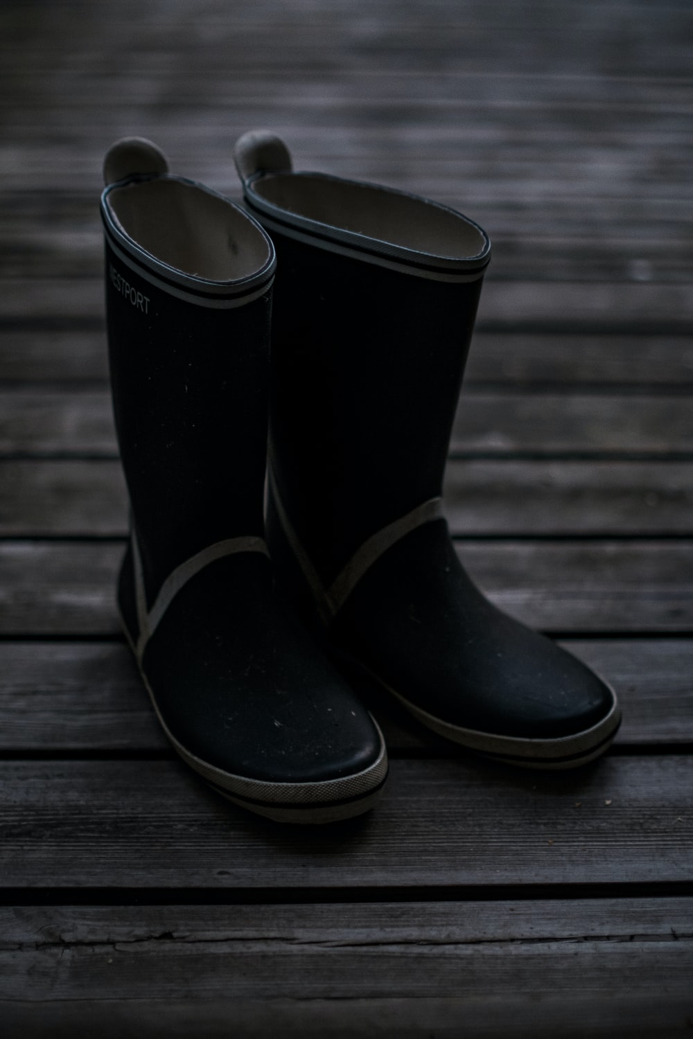 black and white leather boots on brown wooden floor