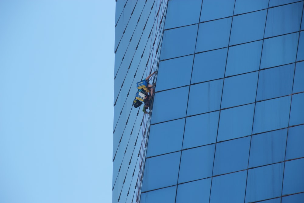 man in yellow jacket and black pants standing on top of building