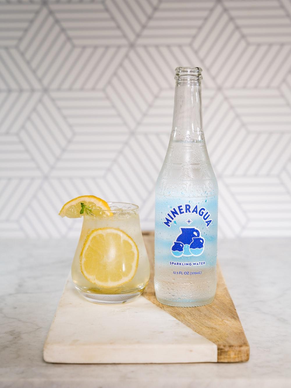 clear glass bottle beside clear drinking glass with lemon juice