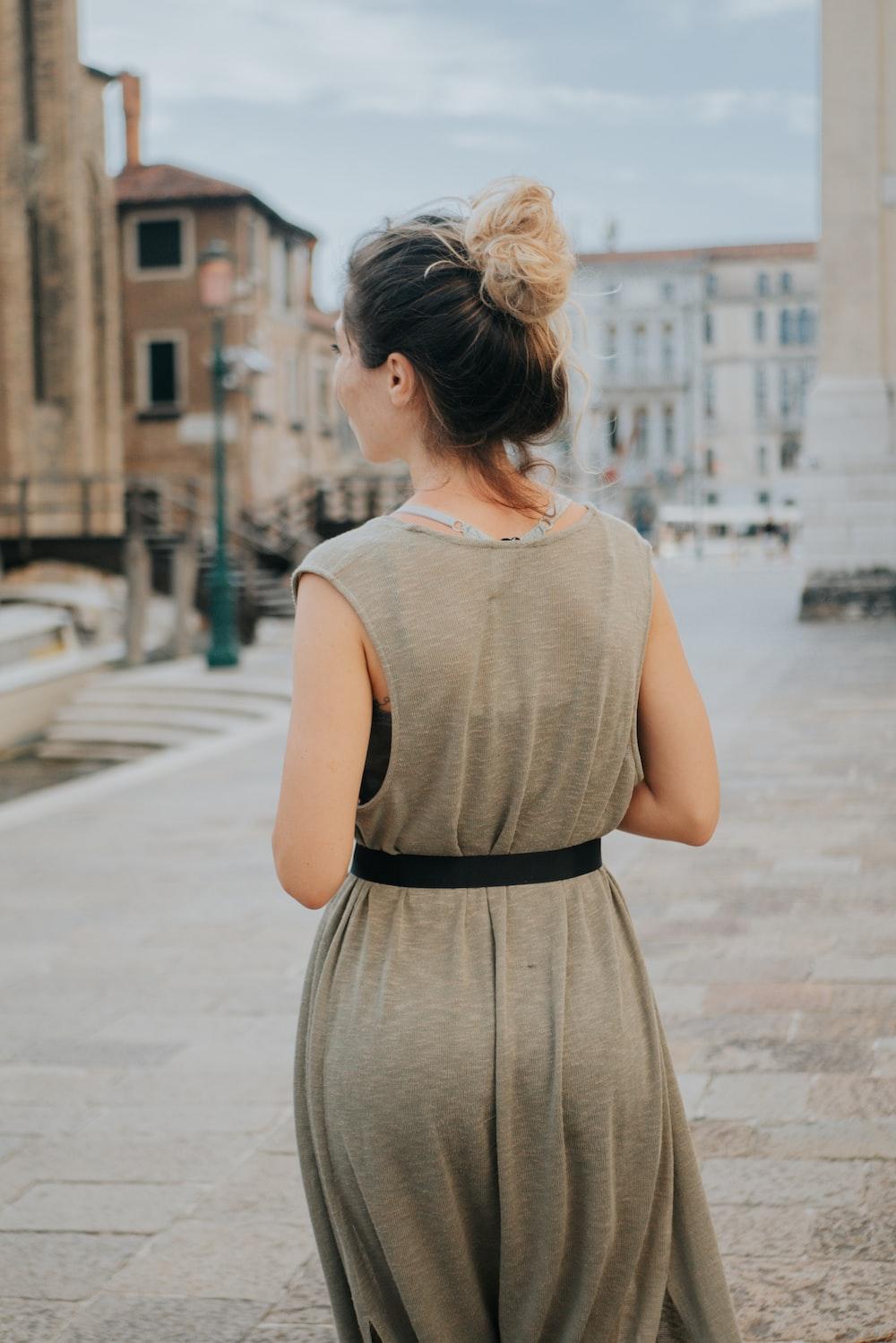 woman in gray sleeveless dress standing on sidewalk during daytime